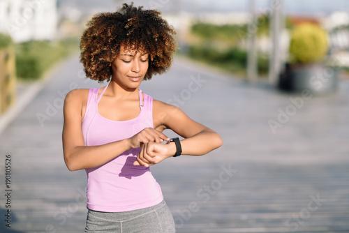 Fototapeta Young black woman using smartwatch touching touchscreen