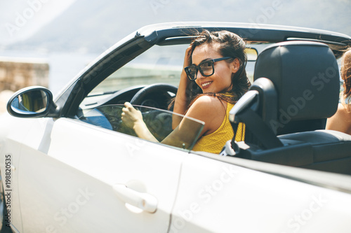 Pretty young woman in white cabriolet car
