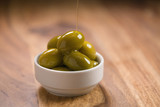 big green salted olives in white bowl on wooden table