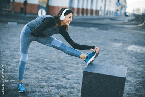 Foto Murales Young sportswoman stretching and preparing to run