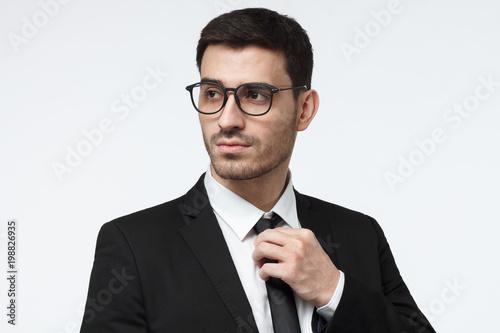 Modny przystojny młody człowiek biznesu trzymając krawat, stojąc na szarym tle z wyrafinowanym wyglądem strony