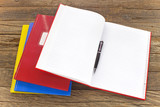 Open notebook with pencil on wooden background