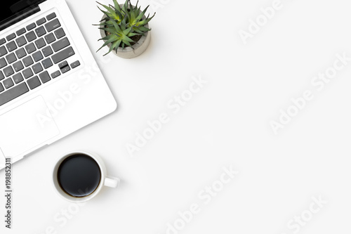 White office desk table with laptop computer and cup of coffee. Top view with copy space, flat lay.