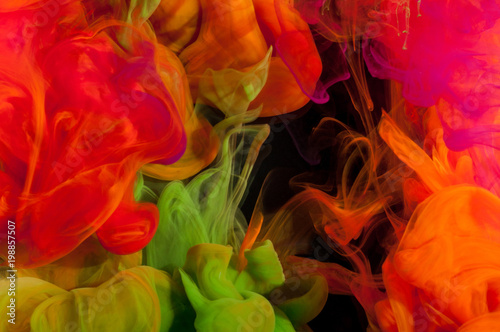 Abstraction of mix multicolored paints in water on a black background - 198857507