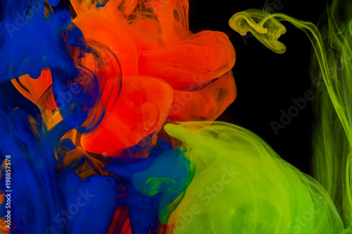 Abstraction of mix multicolored paints in water on a black background - 198857578