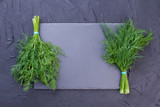 Two bunches of dill and copy space. Fresh organic dill herb on slate board and text space, top view. - 198865568
