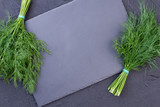 Fresh green fennel on slate board. Two bunches of garden dill on slate board with empty space for text. Why to eat dill. - 198865579