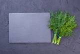 Fresh dill bunches and copy space. Green dill and empty black slate, top view. Dill in culinary. - 198865587