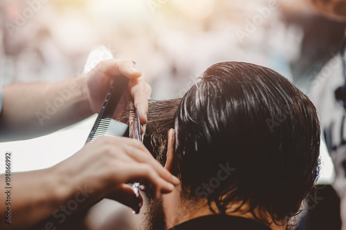 Barbershop. Close-up of man haircut, master does hair styling in barber shop