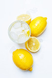 Summer refreshing drink, cold water with ice and lemon, white background, top view