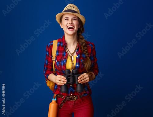 Foto Murales happy healthy traveller woman with binoculars looking up