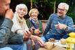 Leinwandbild Motiv Group of cheerful seniors enjoying time together drinking tea outdoors in cafe and sharing life stories in retirement