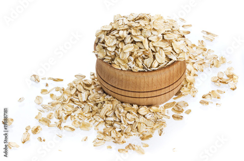 Oat flakes in wooden bowl isolated on white background