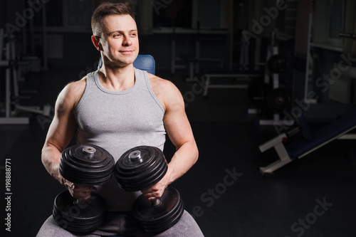Strong handsome fit man exercising in the gym. Personal trainer workout. Athletic man working out his chest with dumbbells on a bench. Fitness, healhty lifestyle, bodybuilding concept.