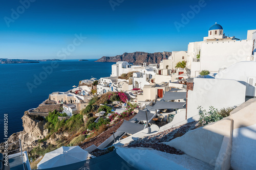Sunrise over Cyclades Island, Greece. Typical white houses on the cliff facing the sea.