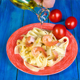 Spaghetti and shrimp in a white dish with a red border, and red tomatoes beside, to, on a blue wooden background. A humans hand pours a dish from a transparent jug with oil.  - 198894366