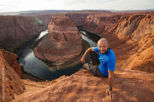 Foto op Canvas Arizona A hiker sitting at the cliff near Horseshoe bend landmark, Arizona, USA