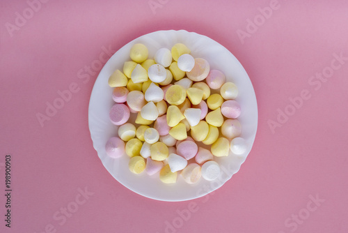 Colorful meringues on plate on pink background