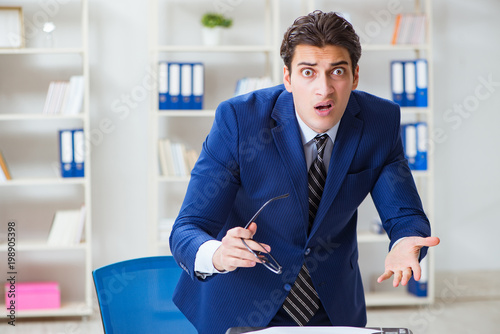 Young handsome businessman employee working in office at desk - 198905398