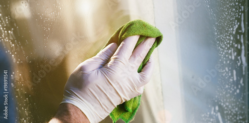 young man is using a rag and squeegee while cleaning windows.