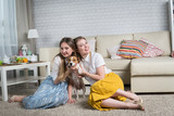 Two young women playing with dog