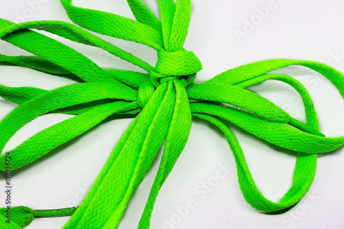 A lace of bright green color tied with a bow on a white background. - 198936724