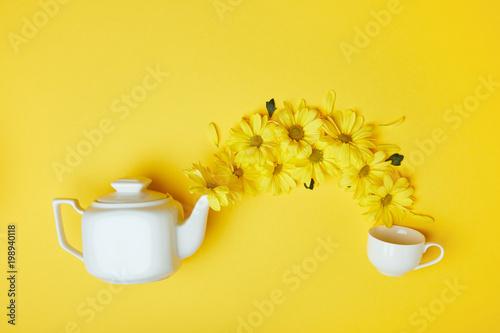 Żółte chryzantemy nalewa w filiżankę od białego garnka odizolowywającego na kolorze żółtym