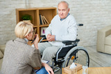 High angle portrait of disabled senior man in wheelchair sharing problems with psychiatrist during therapy session, copy space - 198942994
