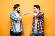 Portrait of a two happy young men giving fist bump