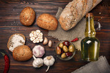 Olives in oil with spices in glass vase and bread on table