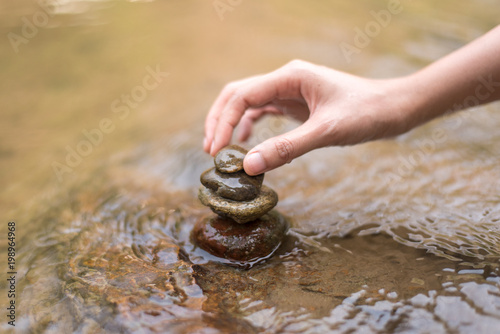 Close up hand to doing Stone stacked in water river - 198964968