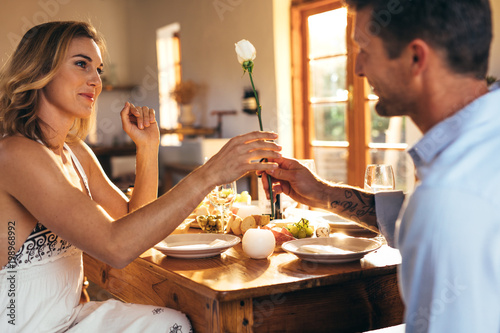 Romantic couple sitting at dining table at home Poster