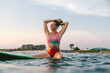 portrait of smiling woman readjusting hair while sitting on surfing board in ocean