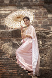 beatiful asian woman wearing thai traditon clothes style with wood umbrella  toothy smiling standing in ayutthaya heritage place - 198986965