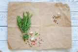 Bunch of rosemary with garlic and spices on wrapping paper - 198992572