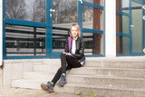 Schülerin sitzend auf einer Treppe vor der Schule