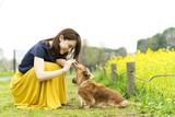女性 ペット 散歩 芝生 花畑