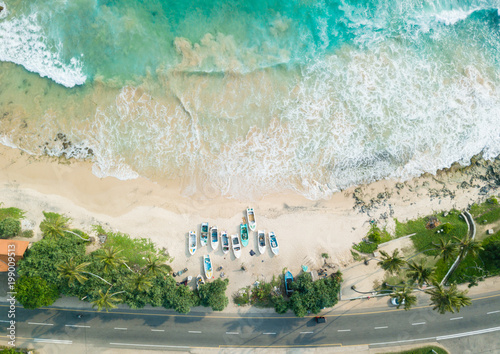 Foto op Canvas Beige Beautiful beach with turquoise water and fishing boats on the beach. Road on the coast of the ocean. Aerial view, drone photography