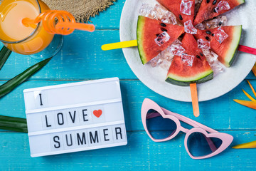Women's casual clothes with accessories items and tropical fruits and flowers on white wooden background, I love summer concept