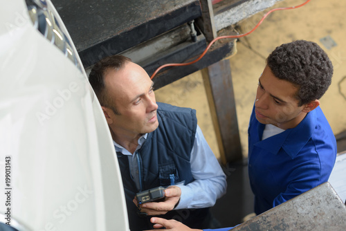 team of mechanics working together in workshop
