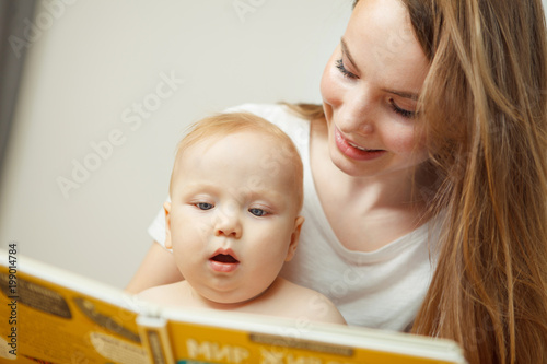 Mother reading to little infant colorful book with fairy tales.