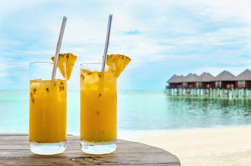 Drinks with a straw on a wooden table on the background of a sandy beach and houses on the water