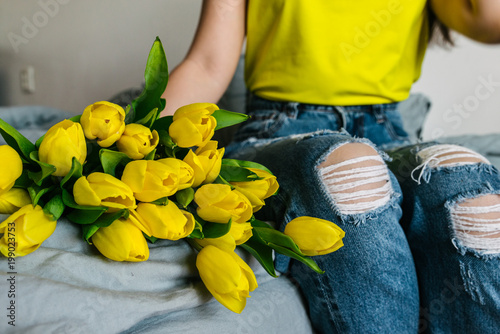 woman hold bouquet of yellow tulips. romantic flowers knees