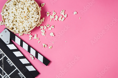 Fresh popcorn and movie clip isolated on pink background top view with copy space around products. Cinematic concept for blogs or design - 199036516