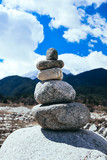 Rocks balancing in a pyramid. Harmony and stability balance concept. Mountain and blue sky on the background. - 199037931