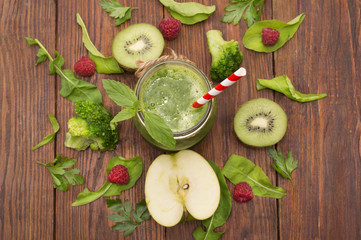 healthy green smoothie with banana, spinach, avocado and kiwi in a glass bottles on a rustic