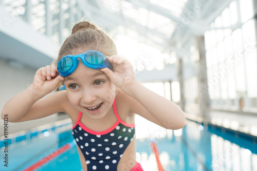 Cheerful emotional girl adjusting swimming goggles and preparing for training on pool enjoying this activity