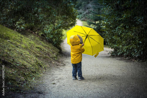 a kid in a park under a yellow umbrella in the rain