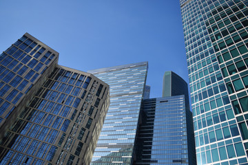 Low angle view of skyscrapers against blue sky