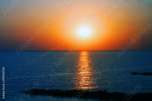 Beautiful sunset on the sea with shallow waves in summer hot evening poster background © mironovm